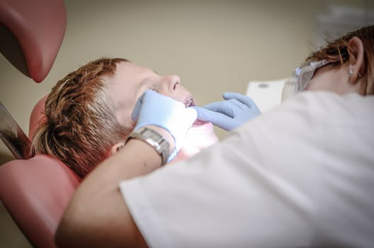 A child lies on a dental chair at Glasgow orthodontics clinic as dental surgeon looks into his mouth.