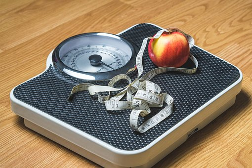 weight loss scales measuring tape and apple